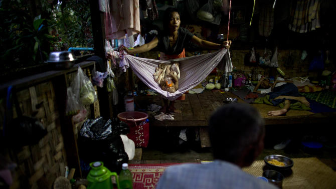 In this Aug. 29, 2012 photo, HIV-infected mother Maw, 36, center, sways a hammock for her 5-month-old daughter Ei Ei Phyu, also infected with HIV, who is sucking a milk bottle, inside a hut shared with other HIV-infected patients at an HIV/AIDS center on the outskirts of Yangon, Myanmar. Following a half century of military rule, care for HIV/AIDS patients in Myanmar lags behind other countries. Half of the estimated 240,000 people living with the disease are going without treatment and 18,000 are dying from it every year.(AP Photo/Alexander F. Yuan)