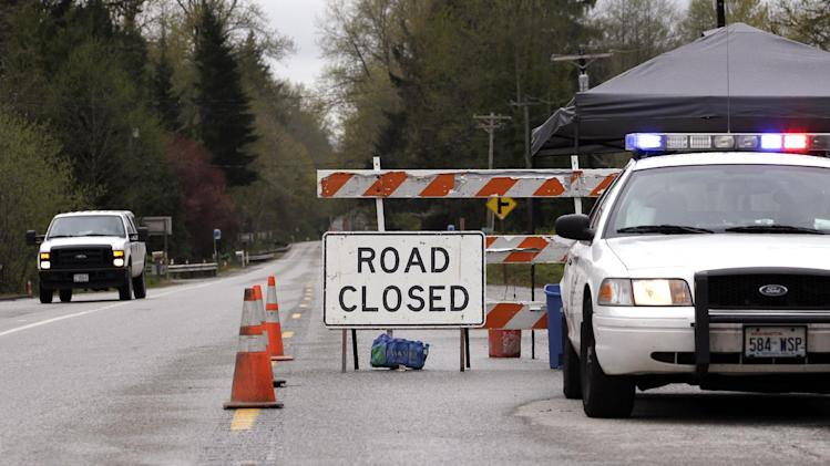 A Washington State Patrol vehicle staffs the closure westbound of Highway 530, Tuesday, April 15, 2014, near Darrington, Wash. One more victim has been recovered from the mudslide that hit the nearby town of Oso, Wash., March 22, raising the death toll to 37, the Snohomish County medical examiner's office said Tuesday. Seven people remain on the missing list, the sheriff's office said. (AP Photo/Elaine Thompson)