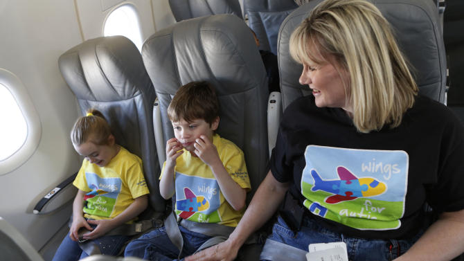 "IMAGES DISTRIBUTED FOR JETBLUE - Cameron Courtney and his sister Joyette sit inside JetBlue plane with their mother Nancy during ""Wings For Autism"" program at Boston Logan Airport on Saturday, April 6, 2013. JetBlue, Massport, TSA and The Charles River Center recently partnered for the ""Wings For Autism"" program in Boston. The program introduces the possibility of travel to children with autism spectrum disorders. (Bizuayehu Tesfaye/AP Images for JetBlue)"