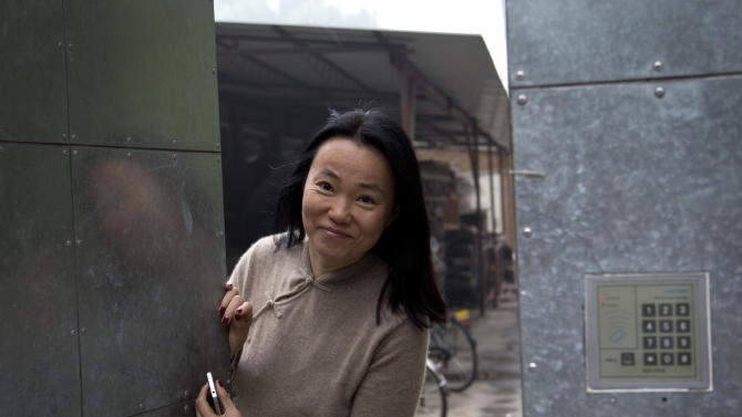 Lu Qing, wife of Chinese dissident artist Ai Weiwei looks from his studio's gate after Ai Weiwei head to the Beijing No. 2 People's Intermediate Court in Beijing Thursday, Sept. 27, 2012. Chinese authorities on Thursday rejected Ai's second appeal of a $2.4 million tax fine, meaning his design company will have to pay the penalty. (AP Photo/Andy Wong)