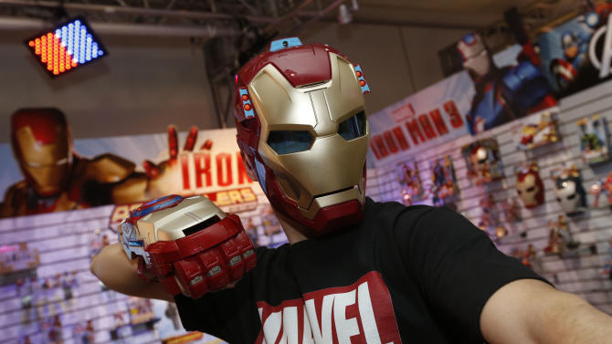 Toy demonstrator Clayton Morris dons the IRON MAN 3 ARC FX MISSION MASK and IRON MAN 3 MOTORIZED ARC FX GAUNTLET, part of Hasbro's IRON MAN 3 line of toys, in the company's showroom at the American International Toy Fair, Friday, Feb. 8, 2013, in New York. (Photo by Jason DeCrow/Invision for Hasbro/AP Images)
