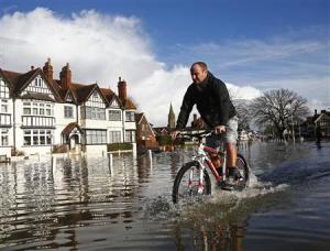 A resident cycles through deep water after the river Thames flooded the village of Datchet