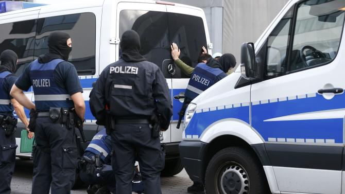Heavily armed masked police officers detain suspect following an early morning raid at 'Cargo City' in Frankfurt airport