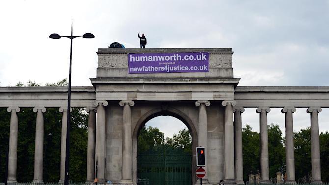 A campaigner from the group New Fathers 4 Justice is pictured on top of the gate of Apsley House at Hyde Park Corner in London on August 15, 2014