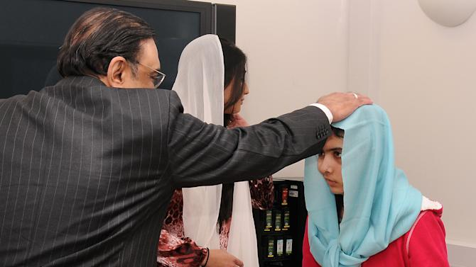 FILE - In this Dec. 8, 2012 file photo provided by the Queen Elizabeth Hospital Birmingham, Pakistan's President Asif Ali Zardari, left, and his daughter Asifa Bhutto, center back, meet with Malala Yousufzai, where she is undergoing treatment for injuries sustained when a Taliban gunman opened fire on her and her friends outside the Khushal School for Girls in Mingora, Swat Valley, Pakistan, at the Queen Elizabeth Hospital in Birmingham, England. Pakistan's High Commissioner to Britain Wajid Shamsul Hasan confirmed a BBC report Wednesday, Jan. 2, 2013 saying that Malala's father, Ziauddin, has been appointed Pakistan's education attache in Birmingham. The position — with an initial 3-year commitment — virtually guarantees Malala will remain in the U.K. where she is undergoing treatment. (AP Photo/Queen Elizabeth Hospital Birmingham, File)