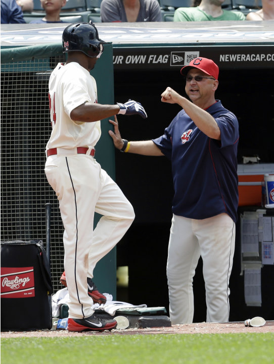 Cleveland Indians manager Terry Francona, right, congratulates Michael Bourn after Bourn scored on a fielders choice by Asdrubal Cabrera in the seventh inning of a baseball game, Monday, May 20, 2013,