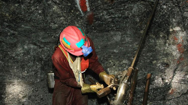 In this photo taken Thursday, Feb. 20, 2014, a miner is photographed underground during a journalist's tour to the South Deep gold mine south of Johannesburg. Miners work some 2.4 kilometers (1.5 miles) underground in 12-hour shifts, where safety is a constant concern and everyone depends on everyone else to stick to precautions. (AP Photo/Themba Hadebe)