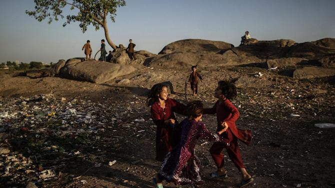 Afghan refugees play in a field on the outskirts of Islamabad, Pakistan, Tuesday, June 18, 2013. Pakistan hosts over 1.6 million registered Afghans, the largest and most protracted refugee population in the world, according to the U.N. refugee agency. (AP Photo/Muhammed Muheisen)