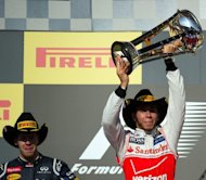 Lewis Hamilton of Britain holds up his trophy after winning the United States Formula One Grand Prix at the Circuit of the Americas in Austin, Texas. Hamilton gate-crashed Sebastian Vettel's title party on Sunday when he produced a dazzling drive for McLaren to win a thrilling United States Grand Prix