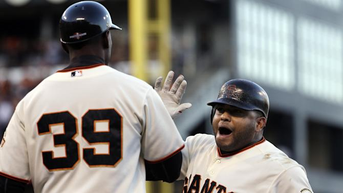 San Francisco Giants first base coach Roberto Kelly congratulates Pablo Sandoval after Sandoval's RBI single during the second inning of Game 6 of baseball's National League championship series against the St. Louis Cardinals Sunday, Oct. 21, 2012, in San Francisco. (AP Photo/David J. Phillip)