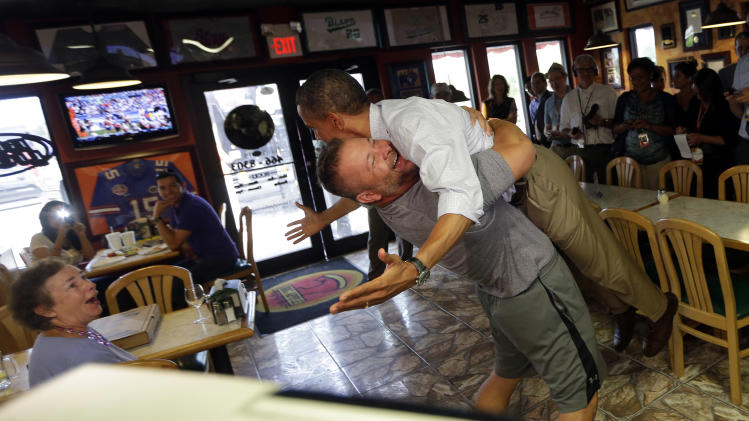 President Barack Obama, right, is picked-up and lifted off the ground by Scott Van Duzer, left, owner of Big Apple Pizza and Pasta Italian Restaurant during an unannounced stop, Sunday, Sept. 9, 2012, in Ft. Pierce, Fla. (AP Photo/Pablo Martinez Monsivais)