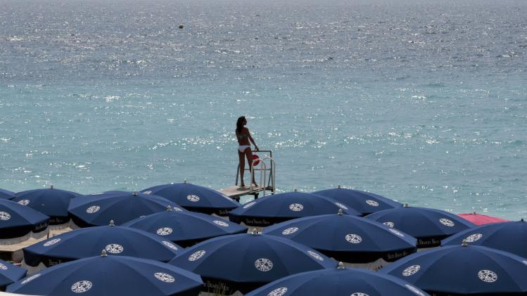 A woman sunbathes on a private beach during a sunny summer day in Nice