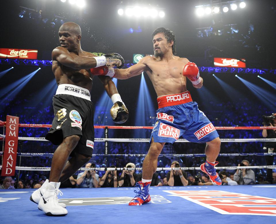 Manny Pacquiao, from the Philippines, right, lands a punch against Timothy Bradley, from Palm Springs, Calif., in their WBO world welterweight title fight Saturday, June 9, 2012, in Las Vegas. (AP Photo/Chris Carlson)