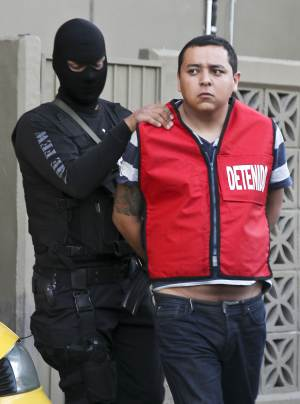 "A police officer escorts Javier Martinez aka ""Javo"", an alleged member of the Zetas drug cartel, during his presentation to the press in Monterrey, Mexico, Tuesday, Aug. 30 2011. Police arrested five alleged members of the Zetas drug cartel suspected of the arson fire at a casino in Monterrey last Thursday that killed 52 people. (AP Photo/Hans-Maximo Musielik)"