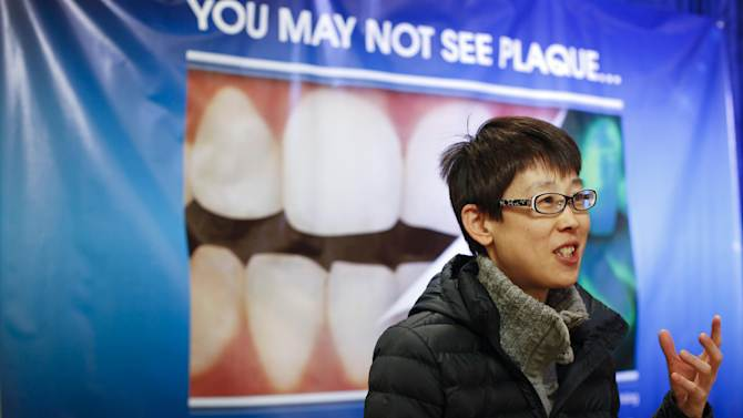 IMAGE DISTRIBUTED FOR CREST ORAL-B - Safeway shopper Junko Tanii reacts to how much plaque is visible on her teeth when using the technology available at a Crest® and Oral-B®  Pro-Health® event in Petaluma, Calif.  on Wednesday, April 10, 2013. Crest and Oral-B are hosting the three day event to help educate people on the plaque that may be left behind. (Alison Yin/AP Images for Crest Oral-B)