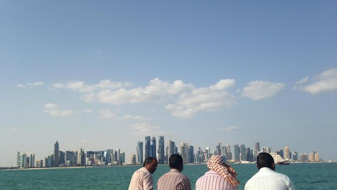 In this photo taken on Nov. 7, 2014, men talk with the Qatar skyline in the background,  in Doha, Qatar. Construction work in underway at a rapid rate as the country prepares to host the Middle East's first World Cup in 2022. (AP Photo/Rob Harris)