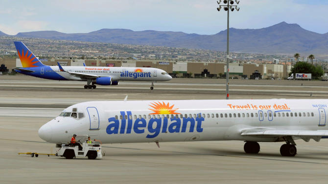 File- In this Thursday, May 9, 2013, file photo, two Allegiant Air jets taxi at McCarran International Airport in Las Vegas. The airline is reporting flight delays nationwide while it inspects emergency slides on its MD-80 aircraft. The Las Vegas-based airline posted a notice on Friday Sept. 20, 2013 apologizing for disrupting customers' travel plans and promising around-the-clock work to correct unspecified problems. (AP Photo/David Becker,File)