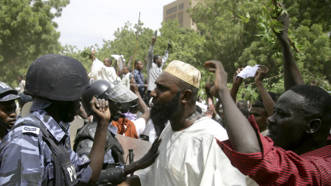Sudanese protesters chant slogans as riot police stand guard in Khartoum, Sudan, Friday, Sept. 14, 2012, as part of widespread anger across the Muslim world about a film ridiculing Islam's Prophet Muhammad. Germany's Foreign Minister says the country's embassy in the Sudanese capital of Khartoum has been stormed by protesters and set partially on fire. Minister Guido Westerwelle told reporters that the demonstrators are apparently protesting against an anti-Islam film produced in the United States that denigrates the Prophet Muhammad.(AP Photo/Abd Raouf)