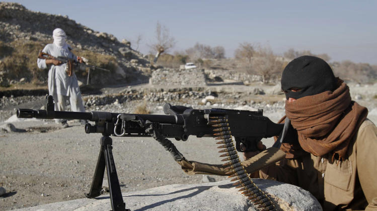 In this photograph made on Monday, Dec. 13, 2010, shows Taliban fighters man a checkpoint in an undisclosed location in Nangarhar province, east of Kabul, Afghanistan. A Taliban commander on the ground said that they were checking the traffic looking for people working for the Afghan government, for non-governmental organizations or who work at the US military bases. (AP Photo)