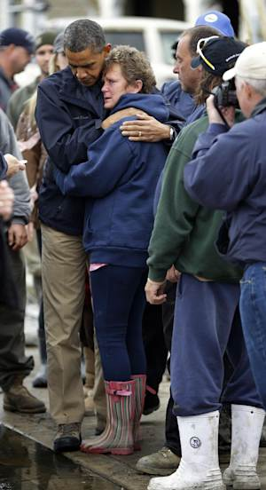 President Barack Obama, left, embraces Donna Vanzant, right, during a tour of an area effected by superstorm Sandy, Wednesday, Oct. 31, 2012, in Brigantine, N.J.  Vanzant is a owner of North Point Marina, which was damaged by the storm. (AP Photo/Pablo Martinez Monsivais)