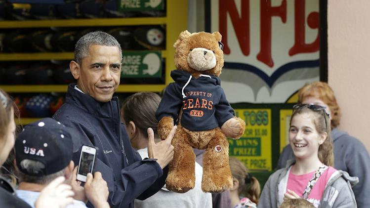 President Barack Obama holds up a stuffed bear that New Jersey Gov. Chris Christie, not shown, had won tossing a football after playing the 'Touchdown Fever' game on the boardwalk during their visit to Point Pleasant, NJ., Tuesday, May 28, 2013. Obama traveled to New Jersey to join Christie to inspect and tour the Jersey Shore's recovery efforts from Hurricane Sandy. (AP Photo/Pablo Martinez Monsivais)