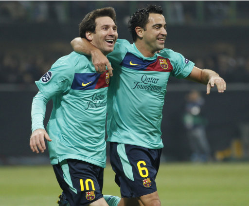 Barcelona forward Lionel Messi, of Argentina, left, celebrates with teammates midfielder Xavi Hernandez after an own goal of AC Milan midfielder Mark Van Bommel during a Champions League, Group H soccer match between AC Milan and Barcelona at the San Siro stadium in Milan, Italy, Wednesday, Nov.23, 2011. (AP Photo/Luca Bruno)