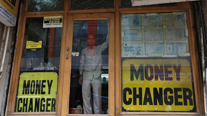 Two men look out from the glass door of a currency exchange shop in New Delhi August 30, 2013. REUTERS/Mansi Thapliyal/Files