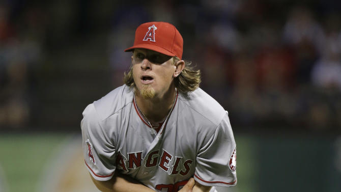 Los Angeles Angels starting pitcher Jered Weaver holds his arm and looks to the dugout after getting hit in the arm with a line drive during the sixth inning of a baseball game against the Texas Rangers Sunday, April 7, 2013, in Arlington, Texas.  Weaver left the game. (AP Photo/LM Otero)