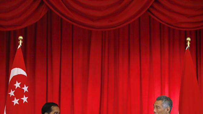 Indonesian President Joko Widodo and Singapore Prime Minister Lee Hsien Loong address a news conference after a signing of memorandum ceremony at the Istana in Singapore