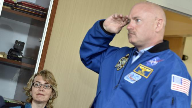 Former U.S. Congresswoman Gabrielle Giffords, left, looks on as her husband Mark Kelly, right, NASA astronaut and commander of mission STS-134, gestures at the Alpha Magnetic Spectrometer (AMS) Payload Operations and Command Center (POCC) at the European Organization for Nuclear Research (CERN) in Meyrin near Geneva, Switzerland, Wednesday, July 25, 2012. Giffords toured the European particle physics laboratory Wednesday, cheerfully facing reporters while surrounded by family and aides but saying little during her first trip abroad since being shot in the head in January of last year. Two days after riding a cable car up into the French Alps, Giffords accompanied her husband, retired astronaut Mark Kelly, on a visit to the European Center for Nuclear Research, which assembled a  US$2 billion cosmic ray detector that Kelly and his team of astronauts carried to the International Space Station.  (AP Photo/Keystone/Martial Trezzini)