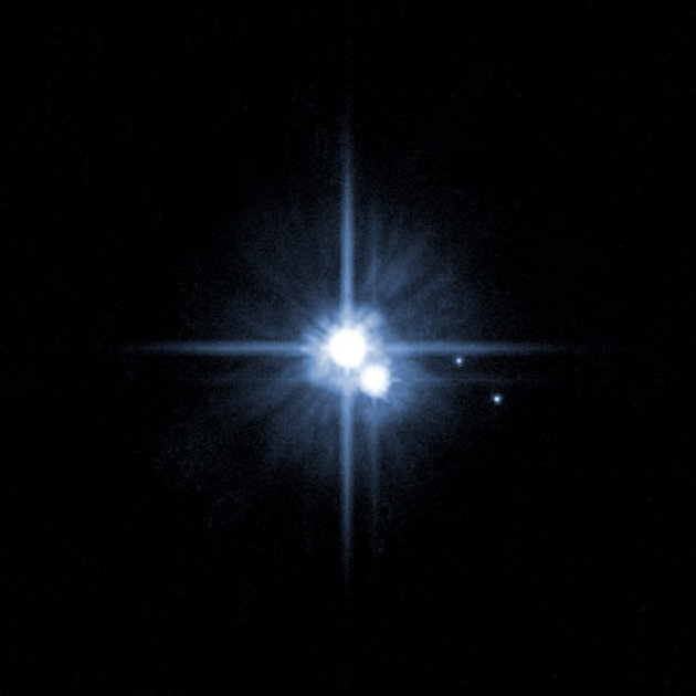 FILE - This file image provided by NASA on Feb. 22, 2006 from it's Hubble Space Telescope shows Pluto and three of it's five moons.  An online vote to name Pluto's two newest, itty-bitty moon conclude