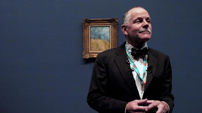 "This Oct. 10, 2012 photo shows Timothy Standring, who curated the upcoming ""Becoming Van Gogh"" exhibit at the Denver Art Museum,  in front of Vincent Van Gogh's ""Edge of a Wheat Field with Poppies,"" in Denver. The museum is installing more than 70 loaned works for its upcoming 12-week ""Becoming Van Gogh"" exhibit, which explores how the self-taught painter developed his signature style. The exhibit runs Oct. 21-Jan. 20. (AP Photo/Thomas Peipert)"