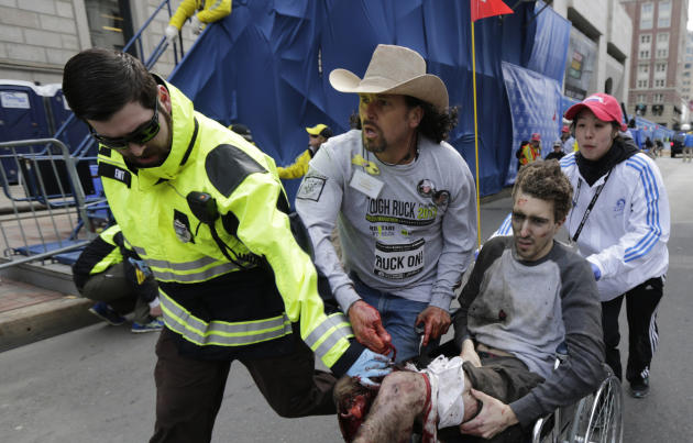 Medical responders run an injured man past the finish line the 2013 Boston Marathon following an explosion in Boston, Monday, April 15, 2013. Two explosions shattered the euphoria of the Boston Marath