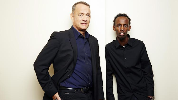 "This Sept. 27, 2013 photo shows actors Tom Hanks, left, and Barkhad Abdi, of ""Captain Phillips,"" in New York. The film, about the 2009 hijacking of the US-flagged MV Maersk Alabama by Somali pirates, opens Oct. 11. (Photo by Dan Hallman/Invision/AP)"