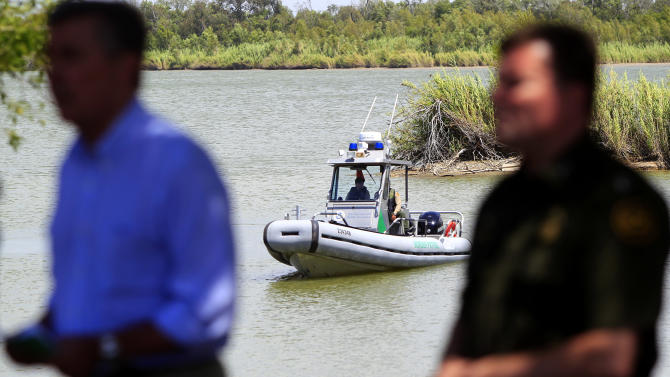 A U.S. Border Patrol boat secures the area as U.S. Customs and Border Protection Commissioner Gil Kerlikowske, left, talks about the dangers of crossing the U.S. border during a news conference for a Danger Awareness Campaign at Anzalduas Park next to the Rio Grande River in Mission, Texas on Wednesday July 2, 2014. The campaign is a Spanish-language outreach effort aimed at highlighting the risks and undercutting the perceived rewards of illegal immigration. (AP Photo/The Monitor, Gabe Hernandez)