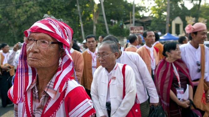 "A Karen ethnic minority representative of Aung San Suu Kyi's National League for Democracy, left, stands in a line to participate in first ever NLD party congress in Yangon, Myanmar, Friday, March 8, 2013. Nearly 900 representatives from across the country stood in neat lines outside the Taw Win (""Royal Rose"") restaurant, waiting to be screened for entry to elect their party leadership for the first time in the NLD's 25-year history. (AP Photo/Gemunu Amarasinghe)"