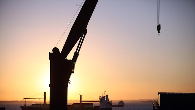 In this picture taken Nov. 29 2013, a cargo ship sails up the Tagus river as the sun rises at Lisbon's Santa Apolonia docks. The European Commission predicts Portugal will return to growth next year, but only at a rate of 0.8 percent, and exports grew almost 10 percent over the 12 months to last September. (AP Photo/Francisco Seco)