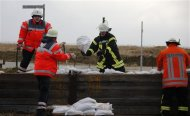 Firefighters reinforce a dyke at the North Sea with sandbags in Sahlenburg, near Cuxhaven, December 6, 2013. REUTERS/Fabrizio Bensch