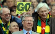 Manchest United supperts standing behind Alex Ferguson at Old Trafford hold up posters calling for the Glazer family to go. Ferguson says he is happy with his club's under-fire owners and their transfer policy