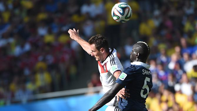 Germany's Miroslav Klose (L) goes head to head with France's Mamadou Sakho during their quarter-final match at The Maracana Stadium in Rio de Janeiro on July 4, 2014, during the 2014 FIFA World Cup