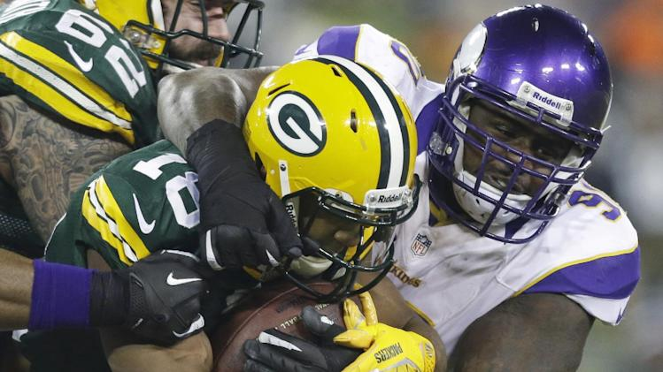 Minnesota Vikings defensive tackle Fred Evans (90) tackles Green Bay Packers wide receiver Randall Cobb (18) during the first half of an NFL wild card playoff football game Saturday, Jan. 5, 2013, in Green Bay, Wis. (AP Photo/Jeffrey Phelps)