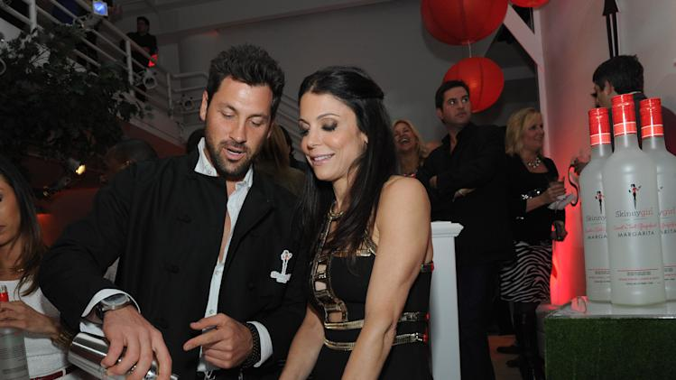 """IMAGE DISTRIBUTED FOR SKINNYGIRL COCKTAILS - The original Skinnygirl Bethenny Frankel jumps behind the bar with friend Maksim Chmerkovskiy at the Skinnygirl Cocktails """"Meet the New Girls"""" launch party, Thursday, April 18, 2013 in New York. The star-studded pair helped unveil Skinnygirl Mojito, Skinnygirl Sweet 'n Tart Grapefruit Margarita, Skinnygirl White Cherry Vodka and Skinnygirl Moscato and tended bar for a good cause as they donated their evening's tips to Dress for Success, with Skinnygirl Cocktails matching the funds raised.  (Diane Bondareff/Invision for Skinnygirl Cocktails/AP Images)"""