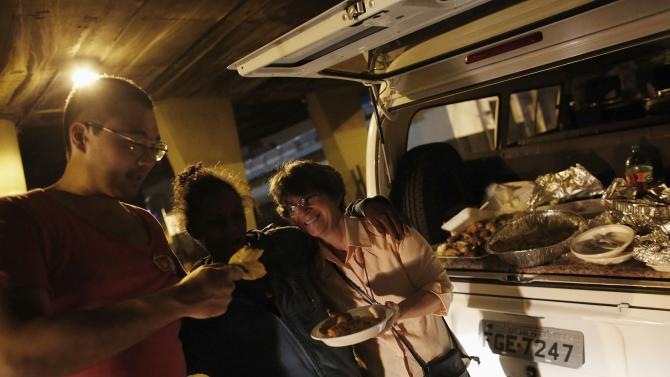 Homeless woman receives food by members of Sao Miguel Arcanjo church on a street during a free Christmas dinner in Sao Paulo