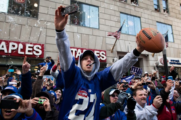 New York Giants fans cheer and reach for autographs from the players during the team's NFL football Super Bowl parade in New York, Tuesday, Feb. 7, 2012. The Giants returned from their Super Bowl win