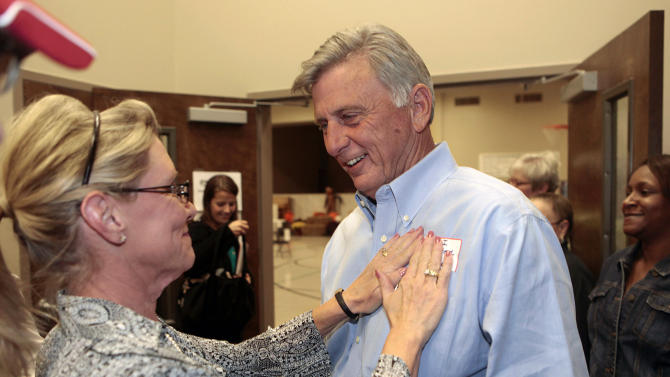 Election official Sharon Carder, left, puts a voting sticker on incumbent Democratic Arkansas Gov. Mike Beebe's shirt in Searcy, Ark., Tuesday, Nov. 2, 2010.  (AP Photo/Russell Powell)