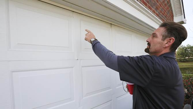 Barry Chipman points put some dents in the garage door of his home in Indianapolis Thursday, Nov. 15, 2012. The Chipman's house is in the neighborhood where an explosion late Saturday evening killed two people, destroyed two homes and made dozens more uninhabitable. (AP Photo/AJ Mast)