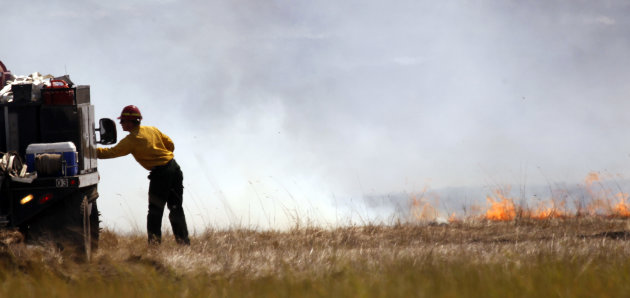 Flames in a smoldering field inch toward a firefighter Wednesday, Aug. 15, 2012, near Cle Elum, Wash. Crews fighting the large blaze in central Washington hope to increase containment levels by Wednesday evening, but are keeping a wary eye on weather conditions later in the week. The fire burning near Cle Elum has burned dozens of homes and caused about 900 people to evacuate. (AP Photo/Elaine Thompson)