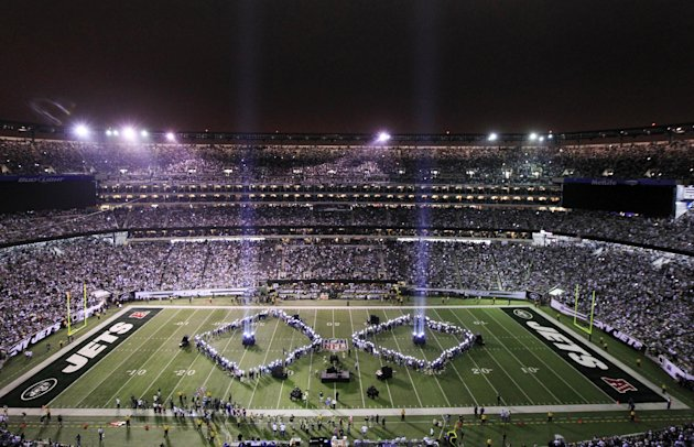 Beams of light rise towards the sky as part of the half time show marking the September 11 anniversary at an NFL football game between the New York Jets and Dallas Cowboys on Sunday, Sept. 11, 2011,