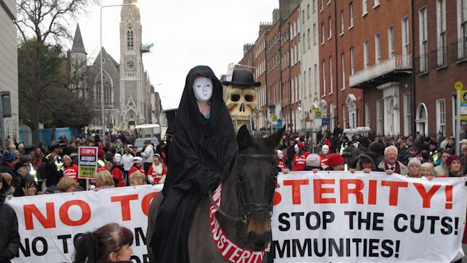 A masked rider on horseback depicting Death leads an anti-austerity protest march in Dublin, Ireland, on Saturday, Nov. 24, 2012. The government says it will unveil Ireland's sixth straight austerity budget next month in hopes of reducing the country's 2013 deficit to 8.6 percent, still nearly triple the spending limit that eurozone members are supposed to observe. (AP Photo/Shawn Pogatchnik)
