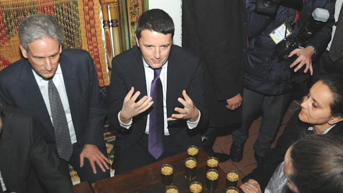 Italian Premier, Matteo Renzi , center, gestures as he shares a glass of tea with pine nuts during a meeting with members of the Tunisian civil society at the cafe des Nattes in Sidi Bou Said, north of the Tunisian capital Tunis, Tuesday, March 4, 2014. Earlier in the day Renzi had met the Tunisian President, Moncef Marzouki, and his Tunisian counterpart, Mehdi Jomaa. (AP Photo/Hamadi Ben Taieb)